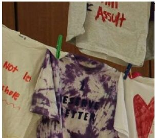 The image of several tees on a clothesline. The tees bear messages from assault survivors.