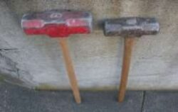 Two sledgehammers stand against a wall, one red and one metal gray.