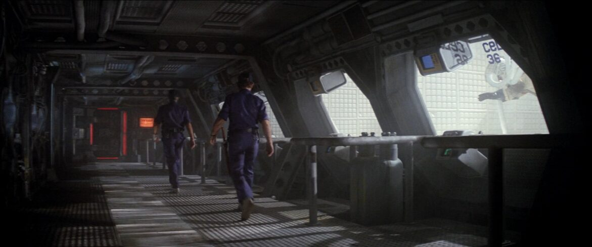 Two men in blue uniforms walk down a metal corridor.