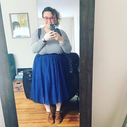 A woman in a striped tee and blue skirt takes a mirror selfie.