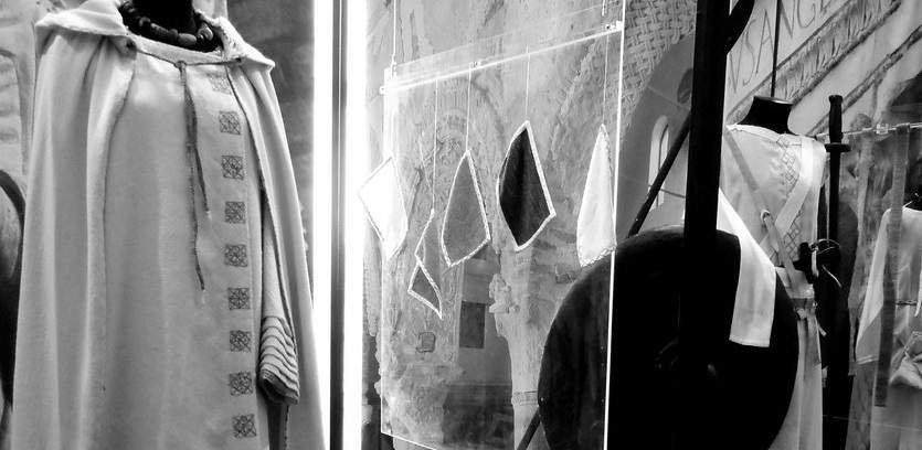 Black and white photo of a dress and cape, cloth swatches, and other clothes.