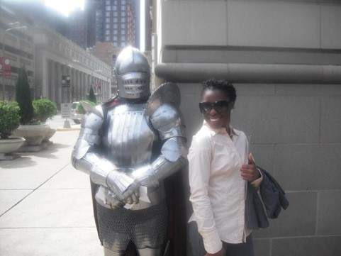 A Black woman in sunglasses, a long sleeved shirt, and holding a jacket smiles at the camera. She stands next to a suit of armor.