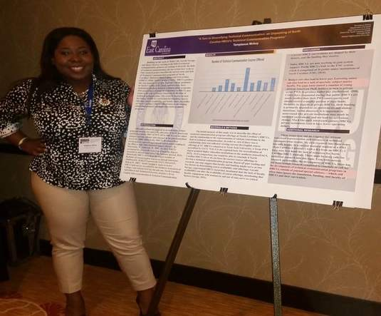 A Black woman in a printed shirt and light pants smiles at the camera. She stands by a conference poster.