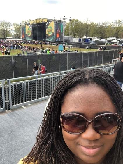 A Black woman in sisterlocs and wearing sunglasses smiles at the camera. Behind her stands a festival stage.