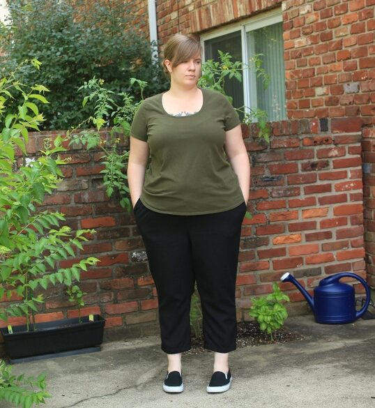 A woman with sideswept bangs and wearing an army green tee and black pants looks off to one side.