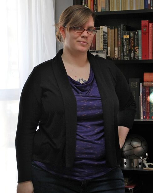 A woman with sideswept bangs and glasses. She wears a purple shirt and a black sweater.
