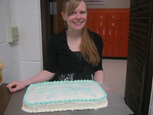 A blonde white woman in a black dress smiles at the camera. Before her on a table is a white iced cake with blue decoration.