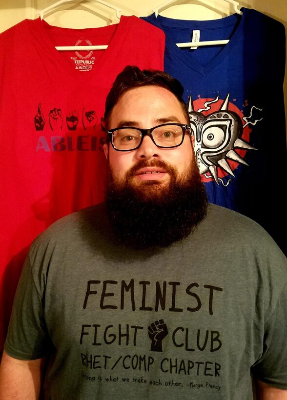 "Man wearing a t-shirt reading ""Feminist Fight Club Rhet/Comp Chapter."" Behind him are two other screen printed t-shirts."