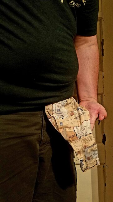 A colostomy bag in a cloth cover hanging from a man's belly.