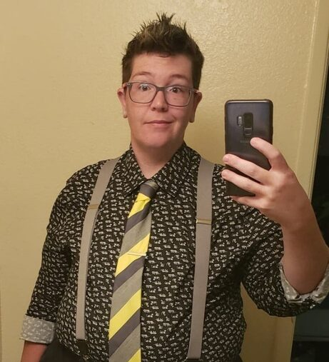 Griffin stands in front of a mirror holding up a phone to take a selfie. They are wearing a black patterned button-up dress shirt rolled up to the elbows, a yellow and grey striped tie, and grey suspenders. They are wearing a bemused and questioning facial expression.